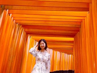 Selene standing in the orange arches of Fushimi Inari in Kyoto