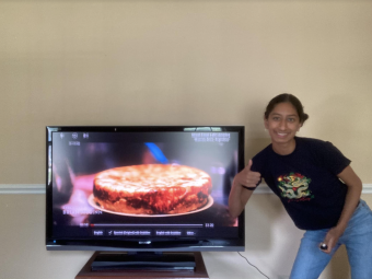 """Keerthi holding a thumbs up in front of a TV screen displaying the docuseries """"Street Food: Latin America."""""""