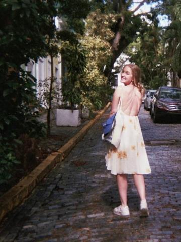 Cary Standing on a stone street with her back facing the camera and turning her head to smile