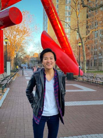 Jackie smilling while standing on locust walk in front of big red sculptures