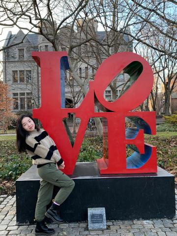 Student standing near love statue