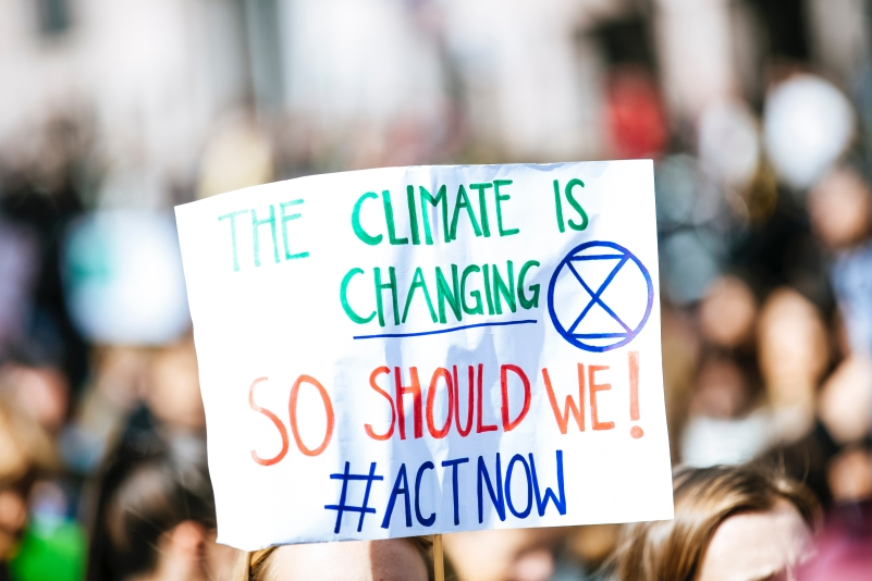 Protesters hold a sign that says 'The Climate is Changing - So Should We! Act Now'