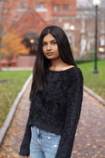 Young woman with long dark hair and black sweater