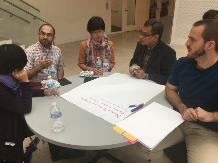 Group of 5 people discussing items to place on a poster